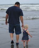 Daddy's little girl. Father and dauther walking to the ocean royalty free stock images