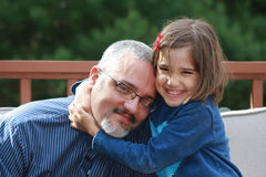Daddy's Princess. An adorable girl is hugging to her dad with a happy expression in her face Stock Photo
