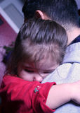 On Daddy's Shoulder. Toddler snuggling into her fathers shoulder royalty free stock images