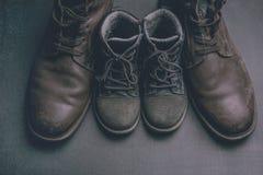 Daddy& x27; s-Stiefel und baby& x27; s-Schuhe, Vatertagskonzept stockfoto