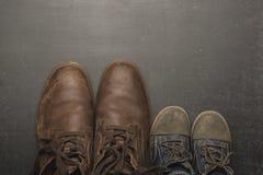 Daddy& x27; s-Stiefel und baby& x27; s-Schuhe, Vatertagskonzept lizenzfreies stockbild