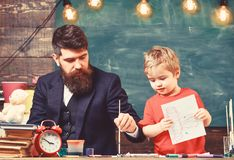 Daddy showing son how to use watercolors. Cute kid holding a drawing in his hands. Creativity concept.  stock photos