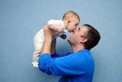 Daddy and the son. The baby bites the daddy nose. The daddy laughs stock images