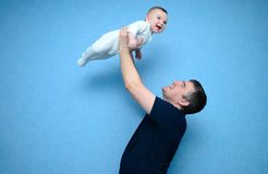 Daddy and the son. Baby in the daddy hands. Blue background stock photography