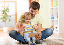 Daddy and son kid playing with tablet computer. Dad and son kid playing with tablet computer indoors Stock Photos