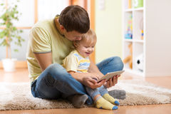 Daddy and son kid playing with tablet computer Royalty Free Stock Images