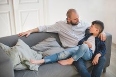 Daddy with son talking and relaxing on sofa. royalty free stock photo