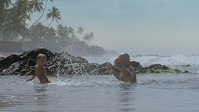 Daddy splashes water on cute boy swimming in warm ocean