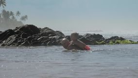 Daddy swims with little boy on back at large stones in sea