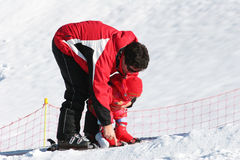 Daddy teaching daughter. How to put on skis Stock Photos