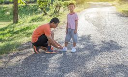 Daddy tie the rope shoes his son on road in the park. royalty free stock photography