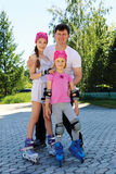 Daddy and two daughters skate on roller skates on a warm summer Stock Image