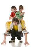 Daddy with two sons. Two sons in coloured sport clothes sit on father shoulders Royalty Free Stock Image