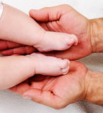 Daddys hands and babys foot Stock Photography