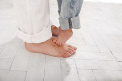 The daddys and his nine months old son feet. Small and big  on white home background Royalty Free Stock Image