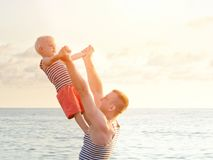 Dade is holding his son in outstretched hands on the seacoast. View from the back Stock Photography