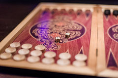 Dadi bianchi del quadrato dell'osso della tavola reale per il gioco con il fondo vago Fotografia Stock