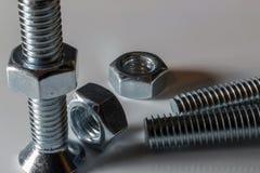 Dadi d'acciaio - e - bulloni con fondo bianco fotografia stock