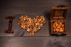 Dadi di amore dell'iscrizione I, dai dadi, noci, mandorle e nocciole ed una scatola di legno marrone con i dadi Fotografia Stock