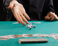 Dadi di lancio dell'uomo su un tavolo verde Fotografie Stock Libere da Diritti