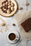 Dadi, dolce di cioccolato e una tazza del cofee sui precedenti bianchi Immagine Stock