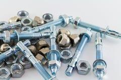 Dadi - e - bulloni d'acciaio su fondo bianco Fotografia Stock