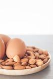 Dadi ed uova della mandorla sul piatto di legno fotografie stock