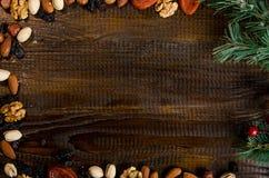 Dadi, frutti secchi, pistacchi e biscotti casalinghi sparsi dalla borsa sulla tavola, attributi del nuovo anno, con un posto per  Immagini Stock Libere da Diritti