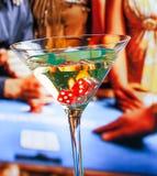 Dadi rossi nel vetro di cocktail davanti al tavolo verde Immagine Stock