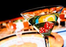 Dadi rossi nel vetro di cocktail davanti alla ruota di roulette Immagine Stock