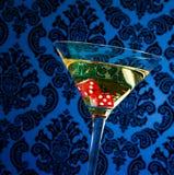 Dadi rossi nel vetro di cocktail su damasco vittoriano d'annata blu Fotografia Stock Libera da Diritti