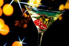 Dadi rossi nel vetro di cocktail sul bokeh e sulle stelle dell'oro Fotografia Stock Libera da Diritti