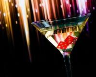 Dadi rossi nel vetro di cocktail sulla pendenza variopinta Fotografie Stock