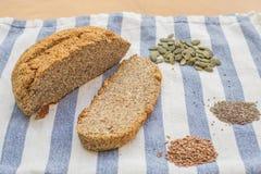Dado e pane stupefacenti dei semi con i semi della zucca, del lino e di chia su un panno della cucina Fotografia Stock Libera da Diritti