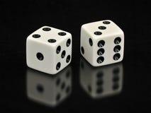 Dados brancos afortunados de Sevens no fundo preto Fotografia de Stock Royalty Free