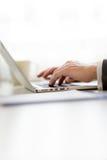 Dados de entrada do homem de negócios em seu laptop Fotos de Stock Royalty Free