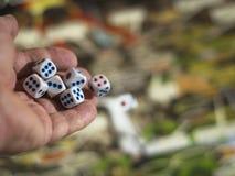 Dados de jogo da mão masculina em um campo verde-amarelo do jogo Fotos de Stock Royalty Free