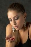Dados de sopro bonitos da mulher nova para a sorte Fotos de Stock Royalty Free