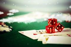 Dados del casino con las fichas de póker en tabla verde del juego fotografía de archivo