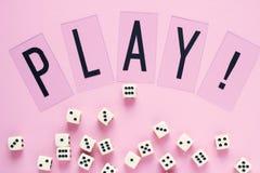 Dados del juego con la palabra JUEGO en fondo rosado Imágenes de archivo libres de regalías