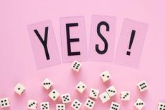 Dados del juego con la palabra SÍ en fondo rosado Fotos de archivo