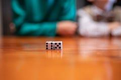 Dados del juego en la tabla con los niños imagenes de archivo