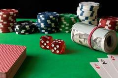 Dados, fichas de póker, naipes y torcido 100 billetes de banco en el th Foto de archivo