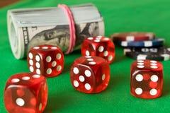 Dados, fichas de póker y torcido 100 billetes de dólar en el tabl verde Imagen de archivo