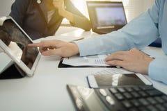 Dados financeiros de discussão executivos do gráfico do plano do acionista na tabela do escritório com portátil e tabuleta foto de stock