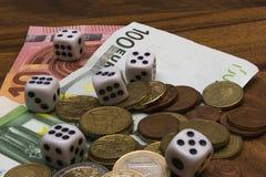 Dados, monedas, billetes de banco euro en una tabla de madera Fotografía de archivo