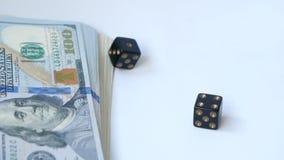 Dados pretos do movimento lento dois, excrementos, jogados no fundo branco, perto de um bloco dos dólares, Conceito do jogo video estoque