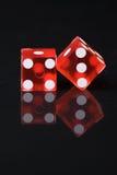 Dados rojos con las pipas blancas en la tabla negra reflexiva fotografía de archivo