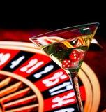 Dados rojos en el vidrio de cóctel delante de la rueda de ruleta Foto de archivo libre de regalías