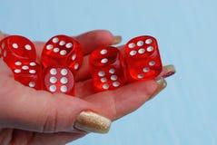Dados vermelhos em uma pilha em uma mão em um fundo azul Imagens de Stock